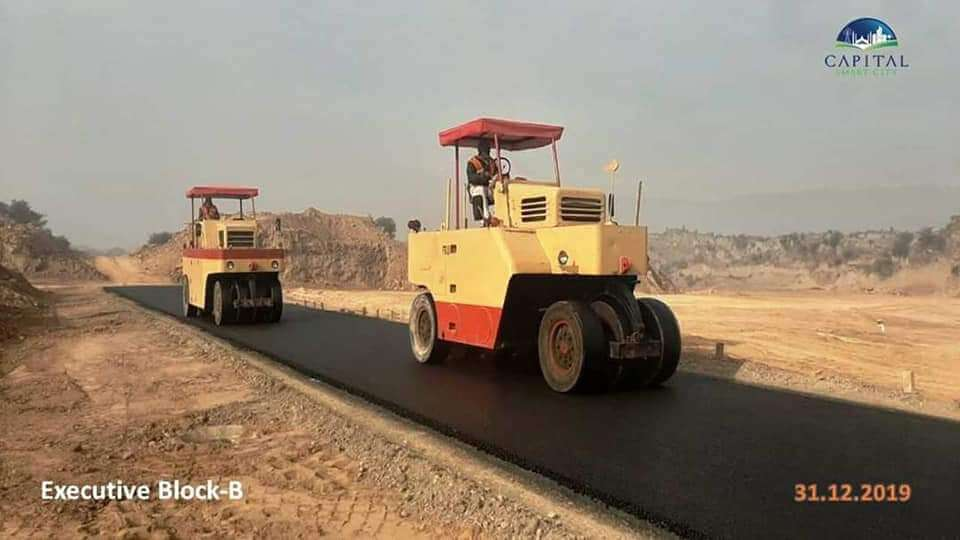 Capital Smart City Executive Block B Construction of carpeted metaled roads with yellow huge road rollers